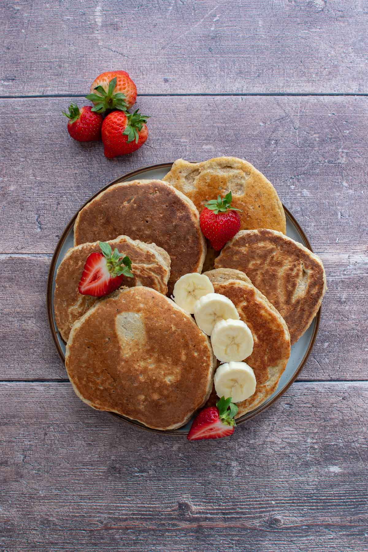 A stack of banana protein pancakes, with strawberries and sliced banana on top.