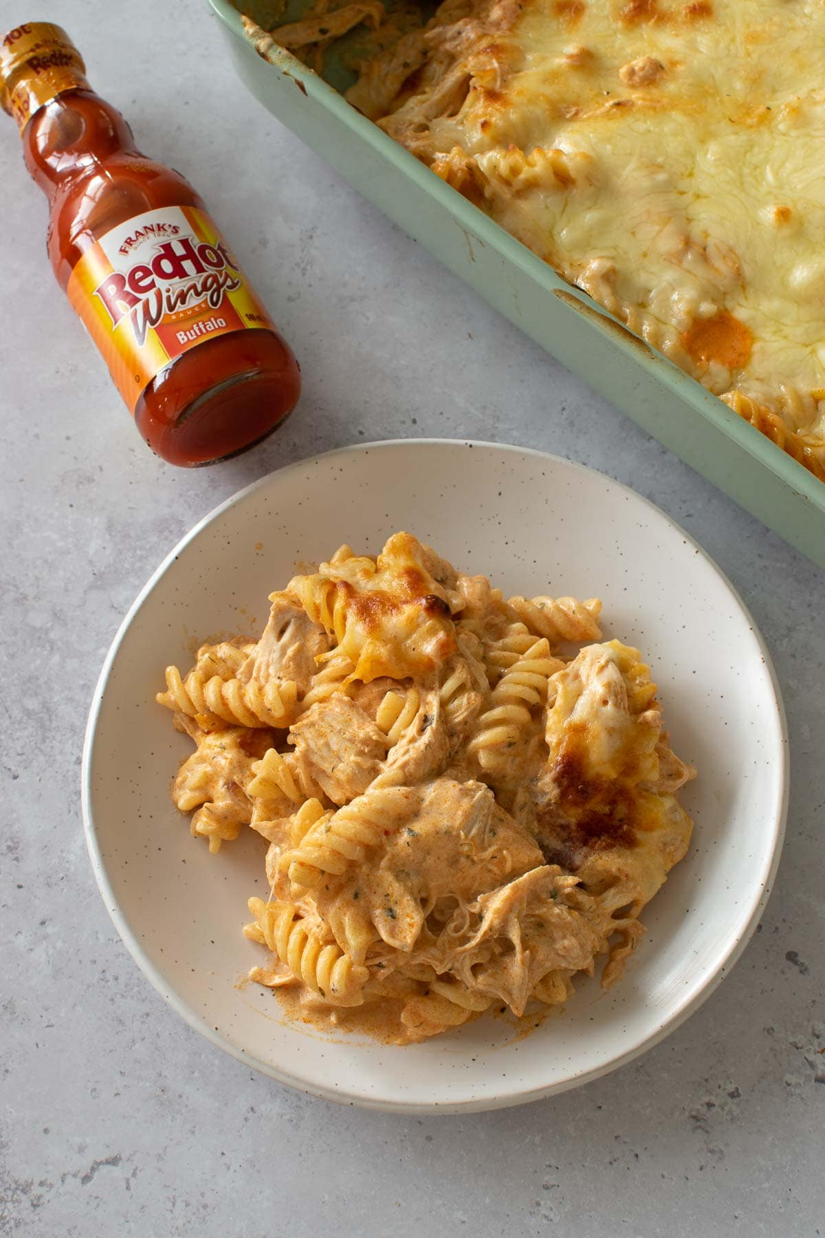 A plate of Buffalo chicken pasta bake with buffalo sauce on the side.