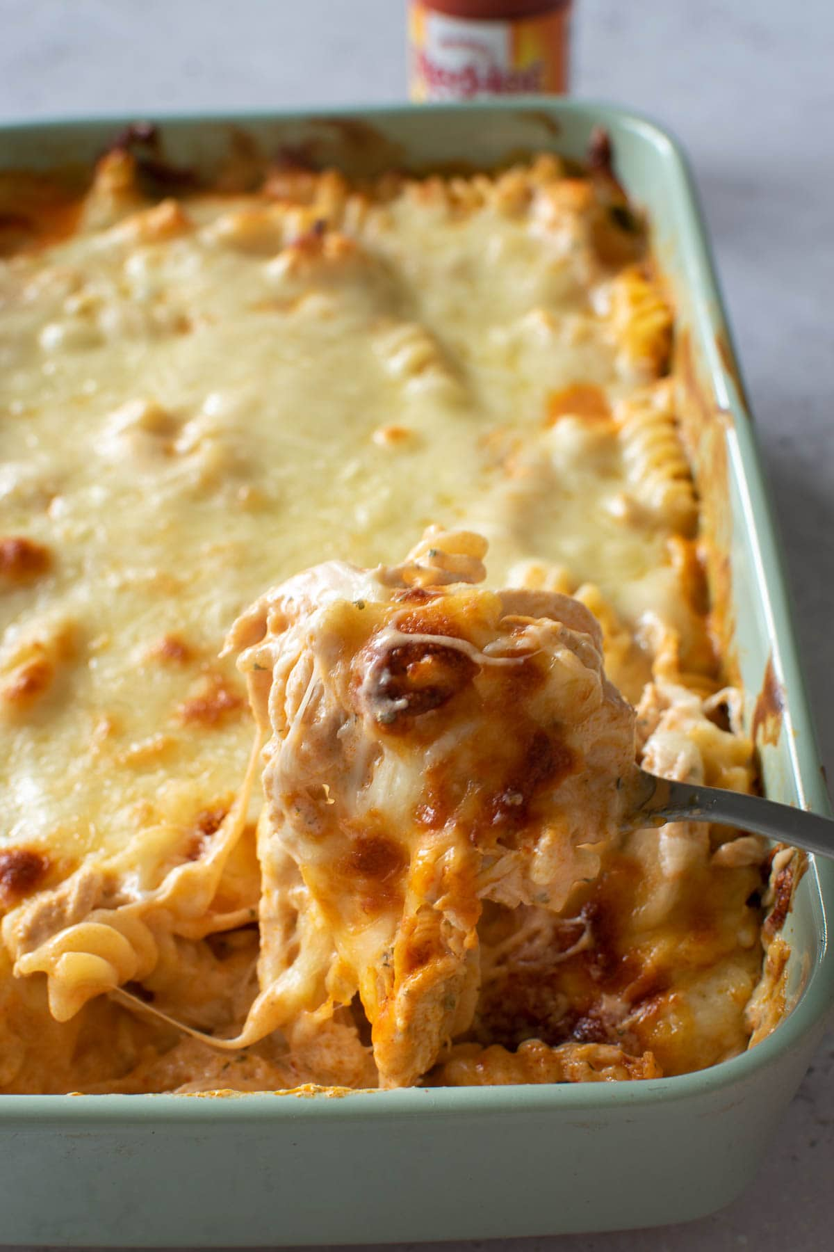Buffalo chicken pasta bake, with a spoon lifting up a cheesy piece.