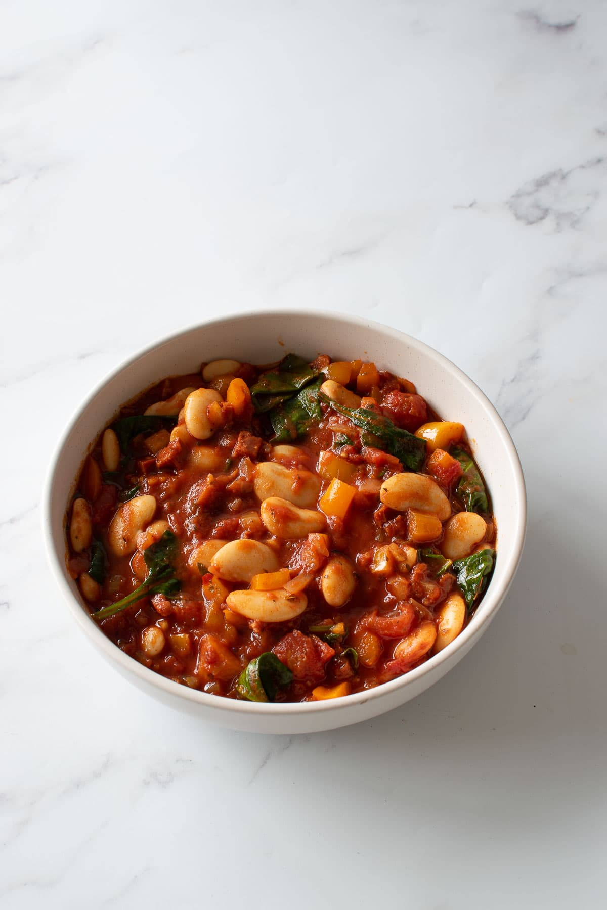 A bowl of stew with chorizo and beans on a table.