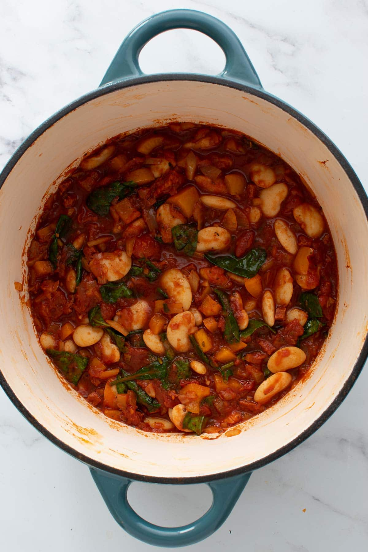 Butter bean stew with chorizo in a blue cast iron pot.