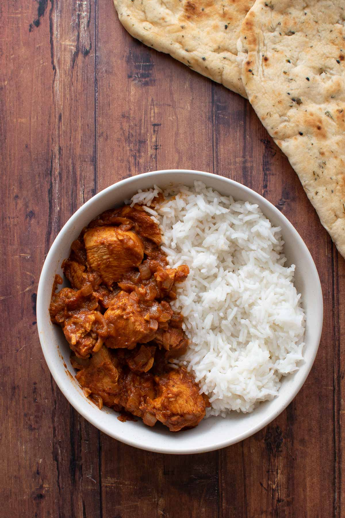 A bowl of chicken rogan josh curry with rice and naan on the side.