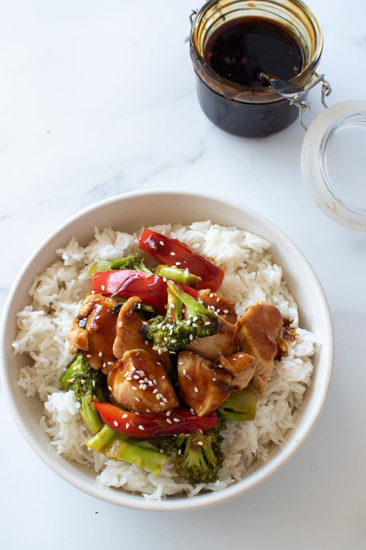 A bowl of rice and chicken stir fry, with a jar of teriyaki sauce in the background.