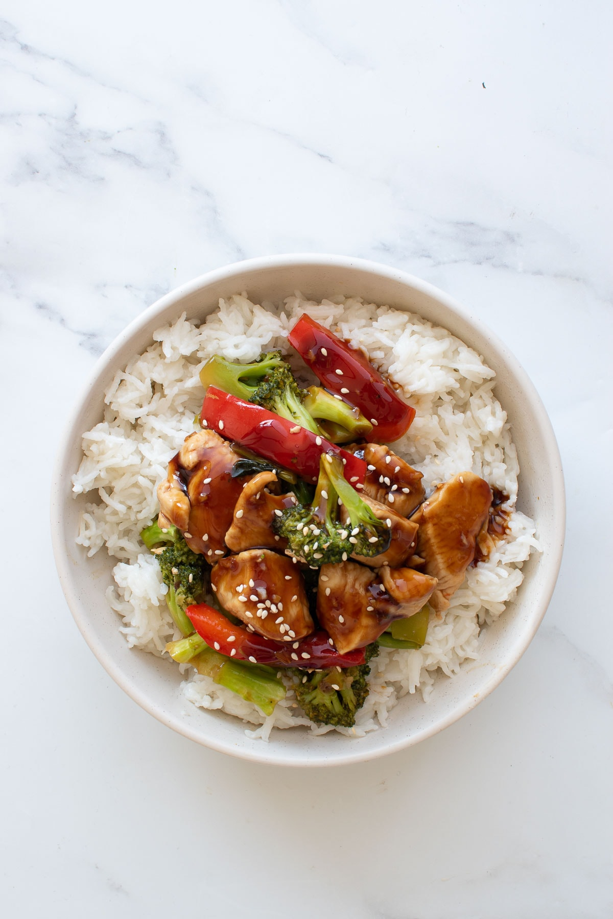 Chicken, broccoli and pepper stir fry with teriyaki sauce on top of rice.