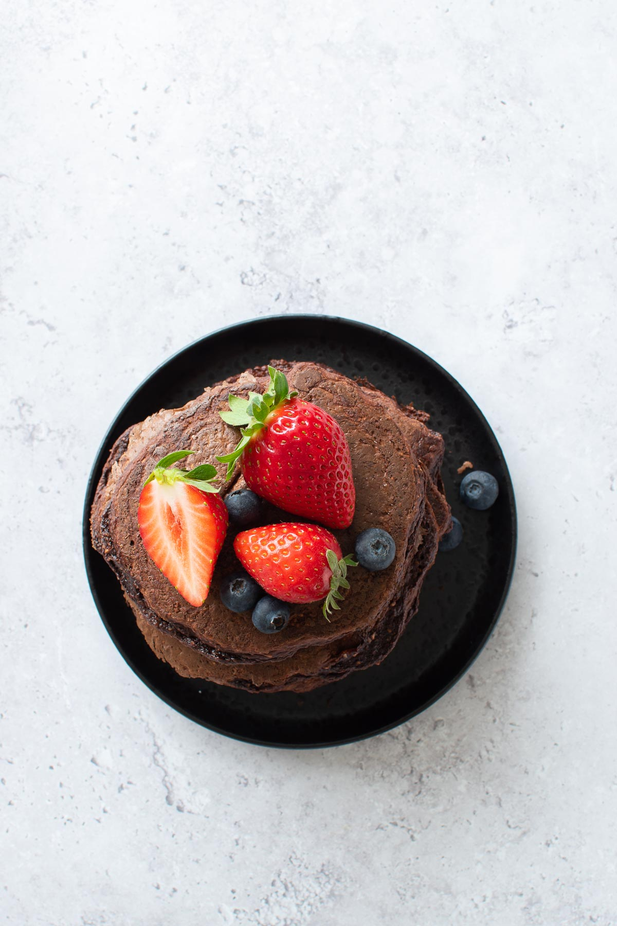 A plate with chocolate pancakes with protein powder.