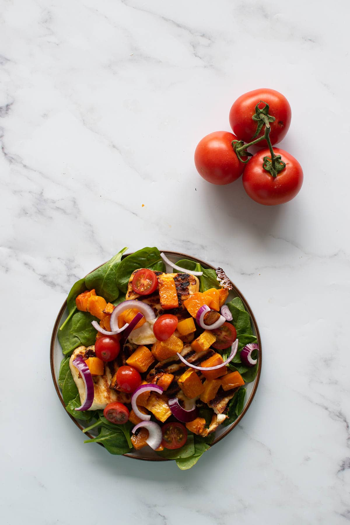A plate of halloumi salad, with tomatoes on the side.