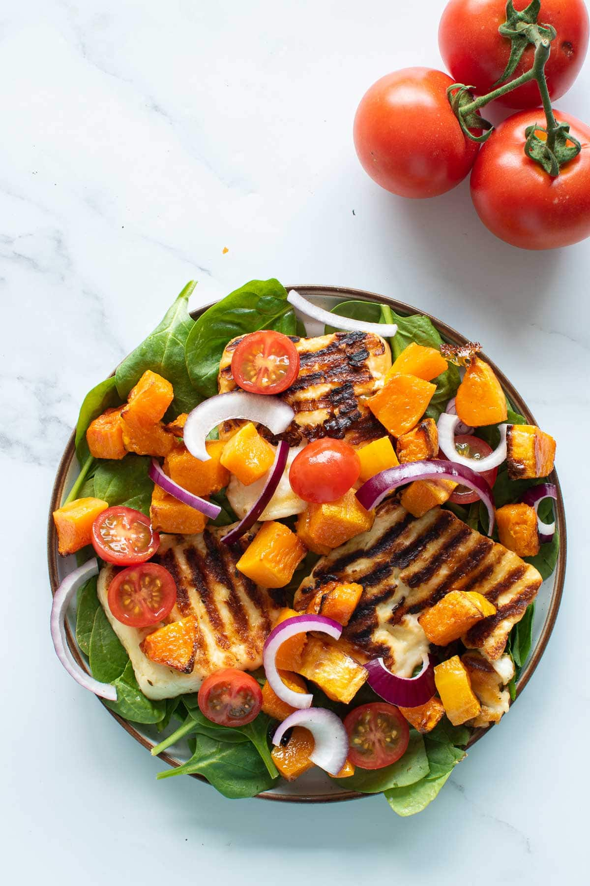 Close up of a plate with halloumi and squash salad.