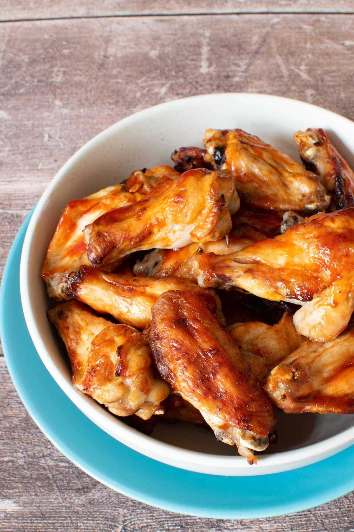 A bowl of chicken wings with sriracha and honey.