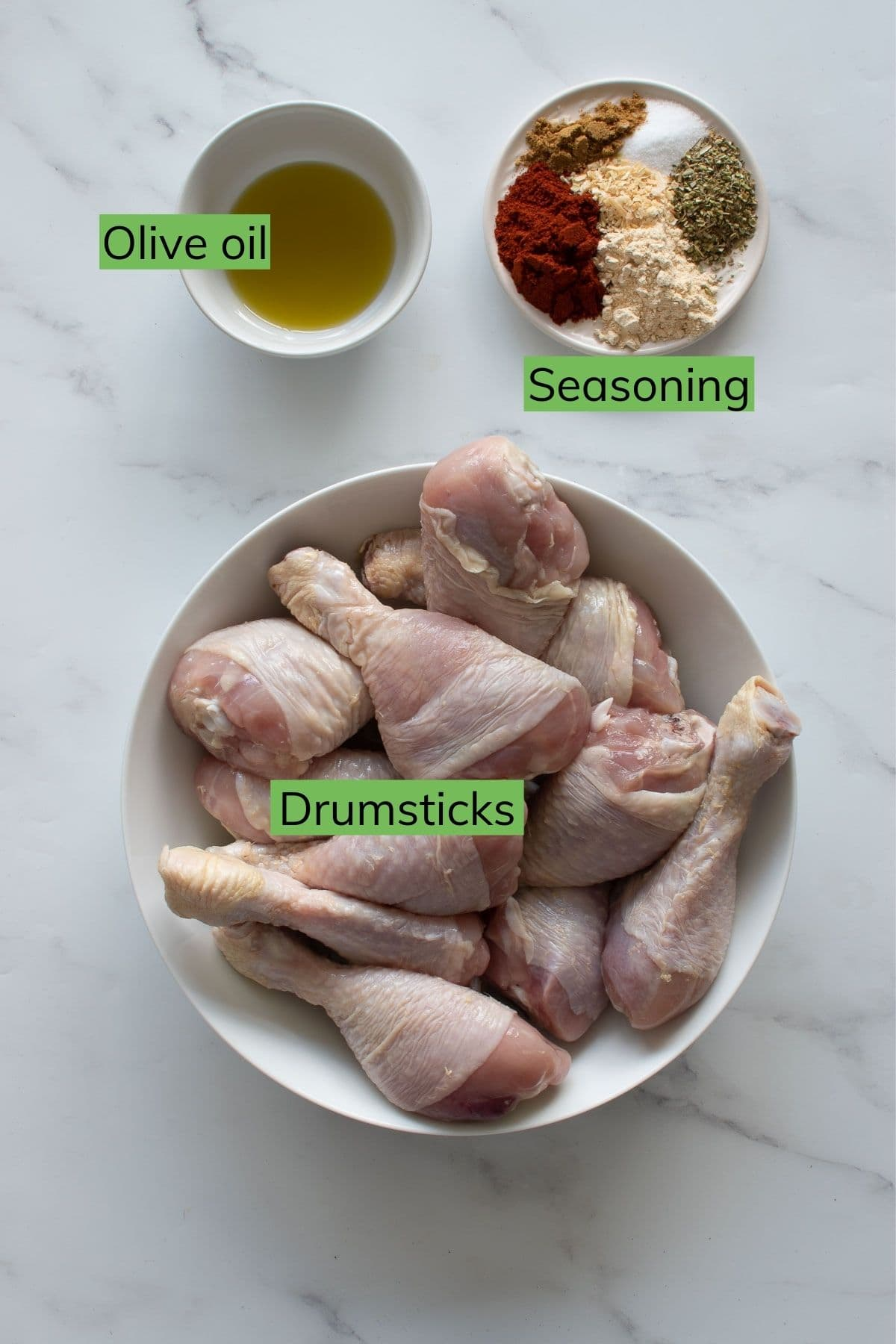 Drumsticks, olive oil and seasoning laid out on a table.