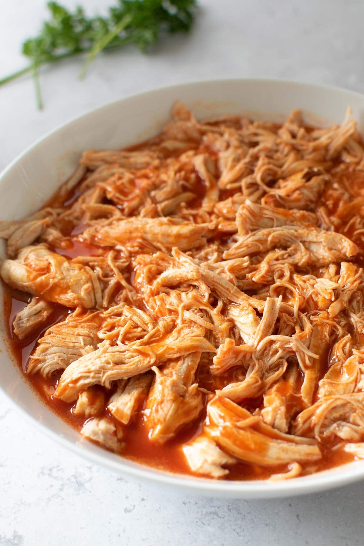 Close up of pulled chicken with buffalo sauce.