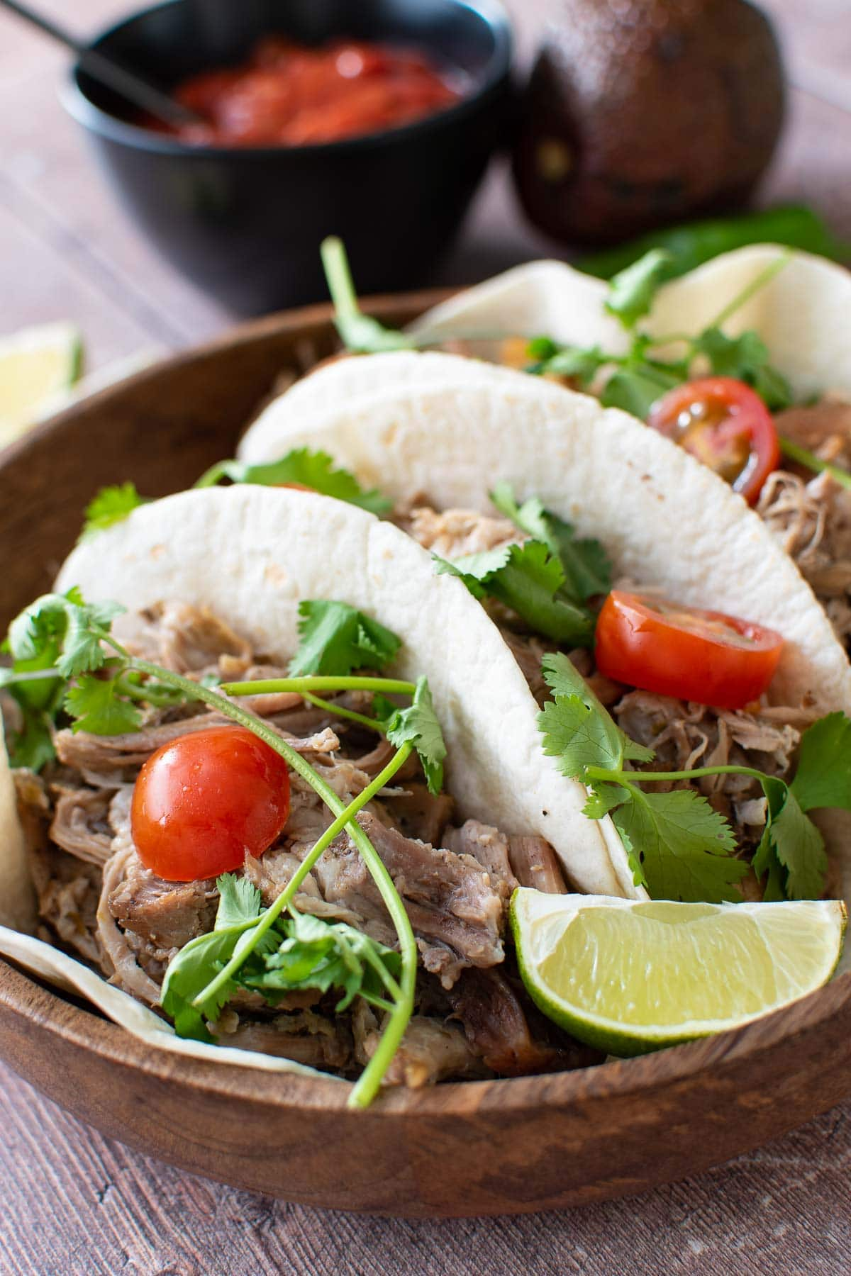 Instant pot pulled pork tacos with tomatoes, lime and cilantro.