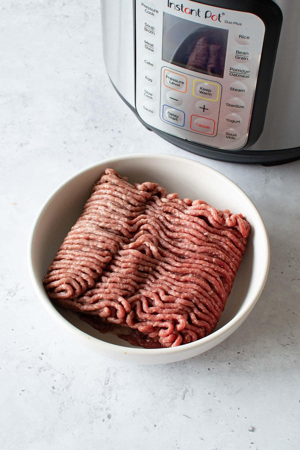 Ground beef in front of an Instant Pot.