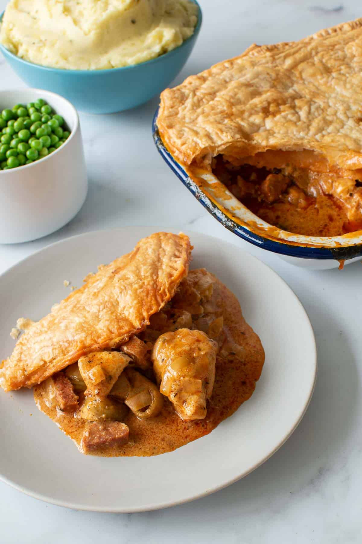 A plate of chicken and chorizo pie, with the pie, mashed potatoes and peas in the background.