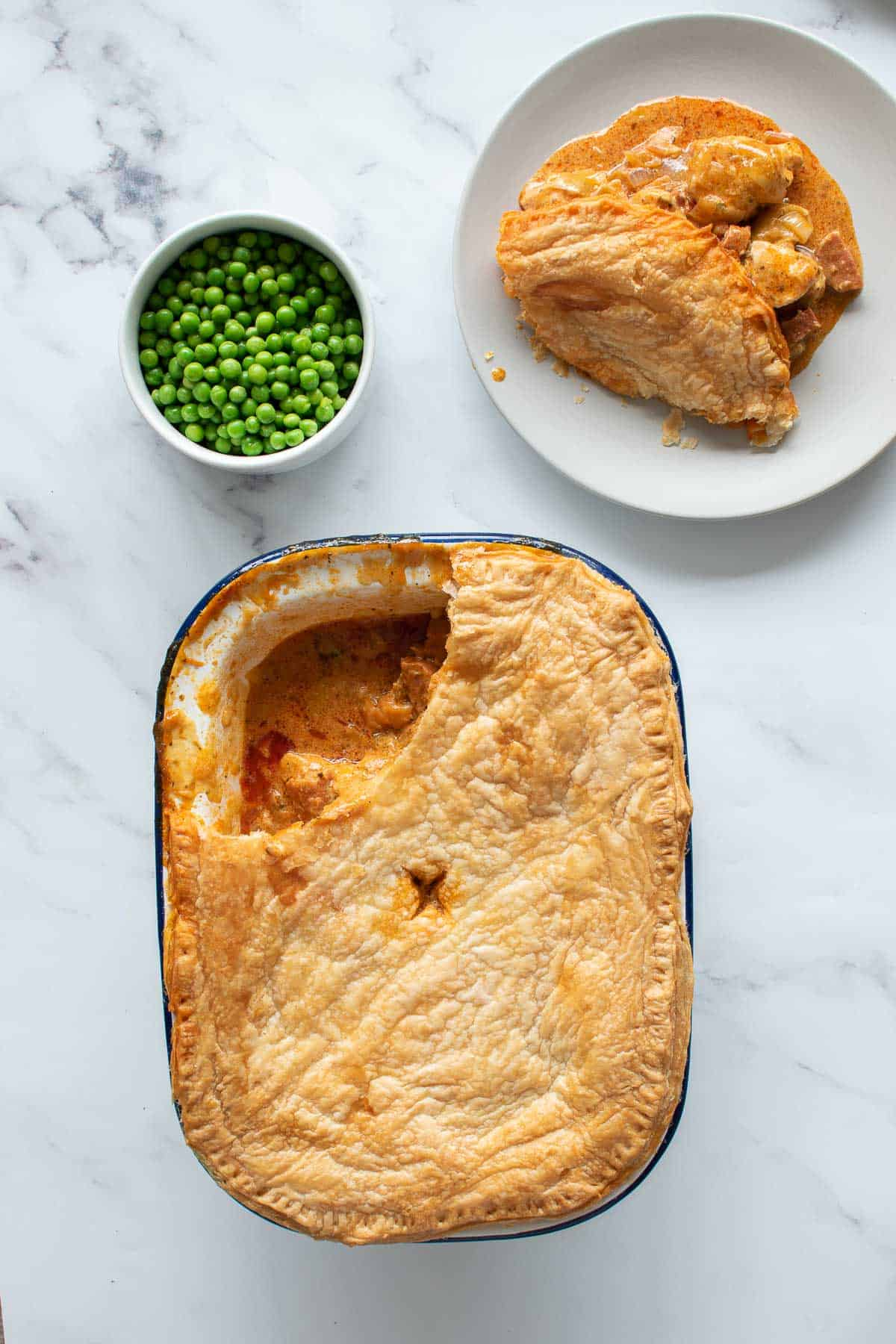 Pie with chicken and chorizo, with a serving placed onto a plate and a bowl of peas on the side.