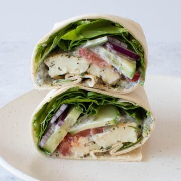 Close up of halloumi wraps with spinach, tzatziki and tomatoes.