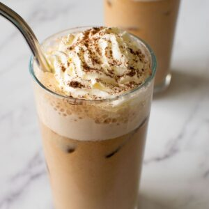Close up of iced latte with whipped cream.
