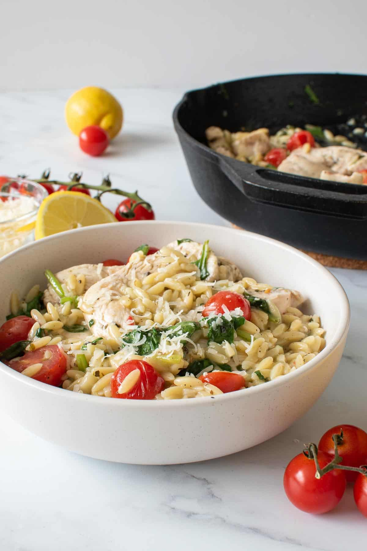 A bowl of lemon chicken with orzo and tomatoes, with a cast iron skillet in the background.