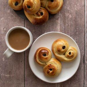 Lussekatter on a plate, with a cup of coffee on the side.