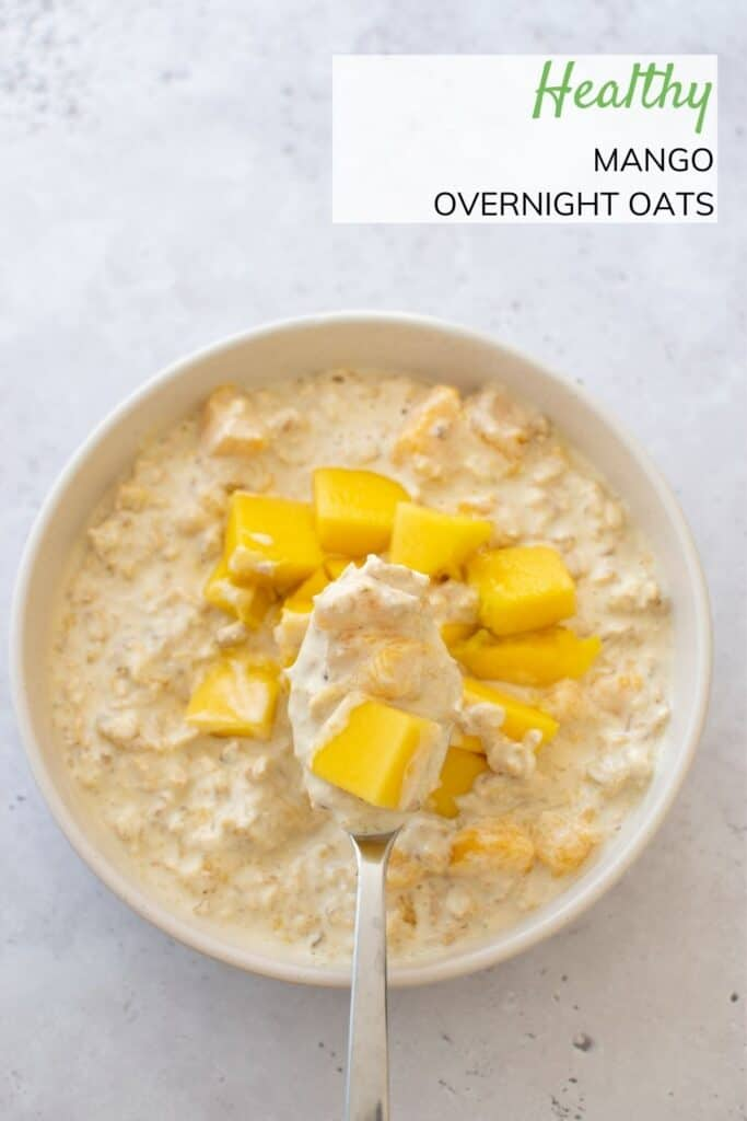A bowl of mango overnight oats, with a spoon.
