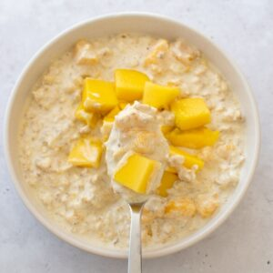 A spoon filled with creamy mango oats.