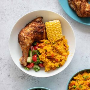 Peri peri chicken with rice, corn on the cob and salad.