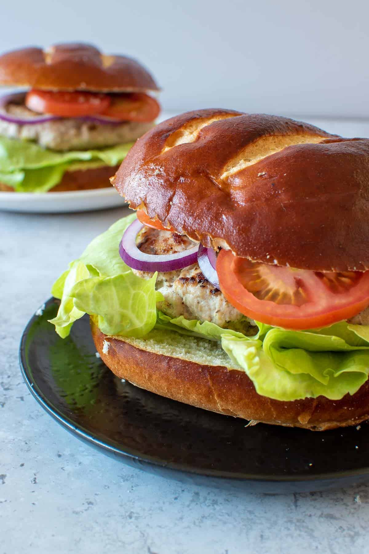 Two plated pork burgers.