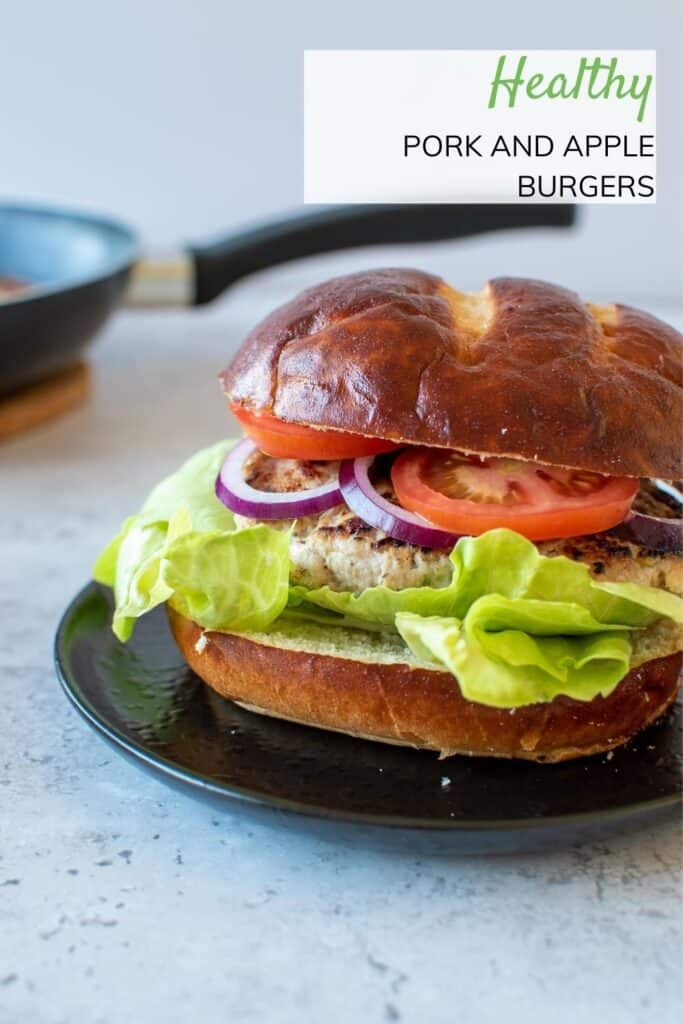 A pork burger in a bun, with tomatoes, lettuce and onions.