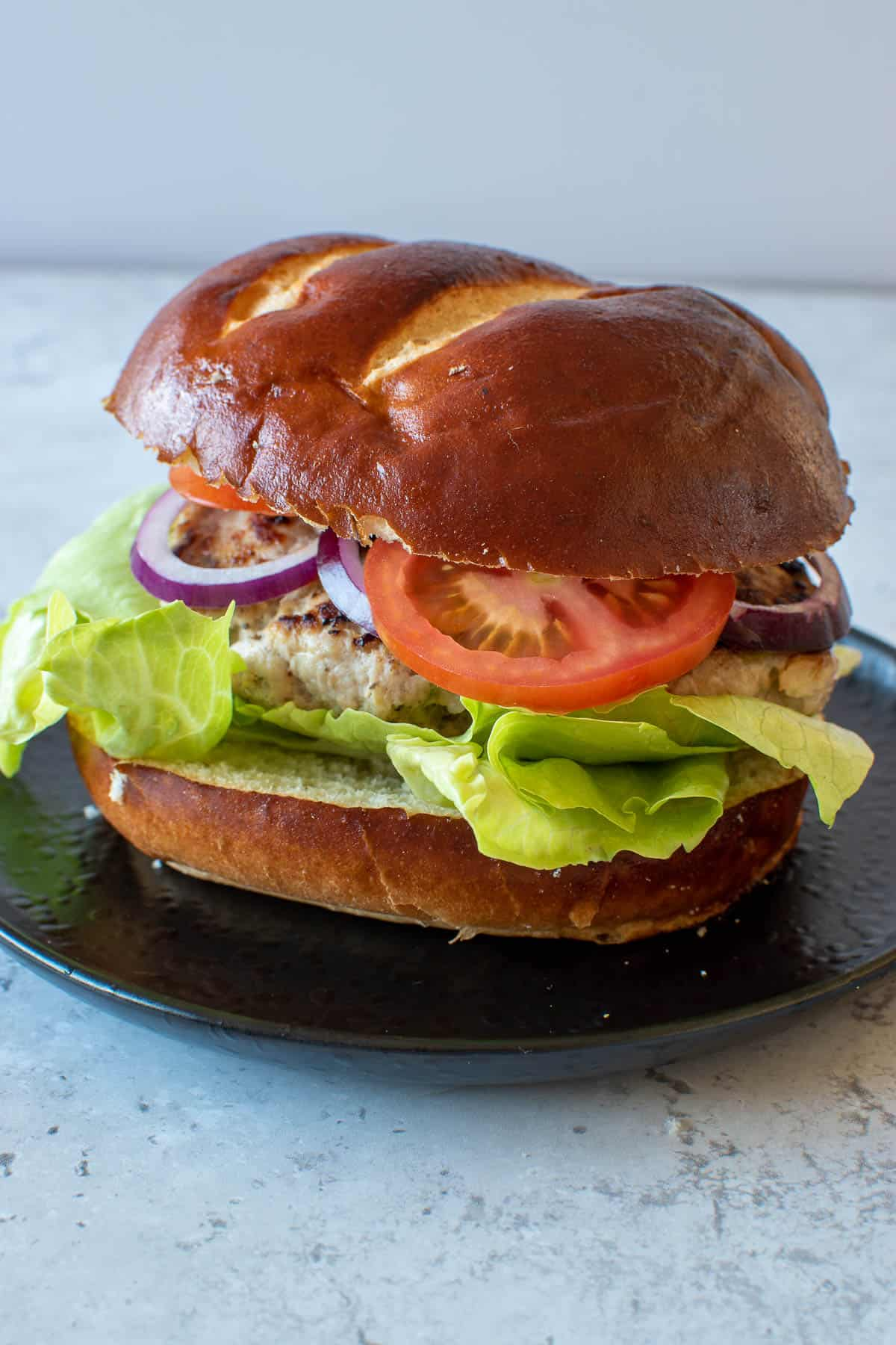 A pork apple burger with lettuce, tomato and onion.