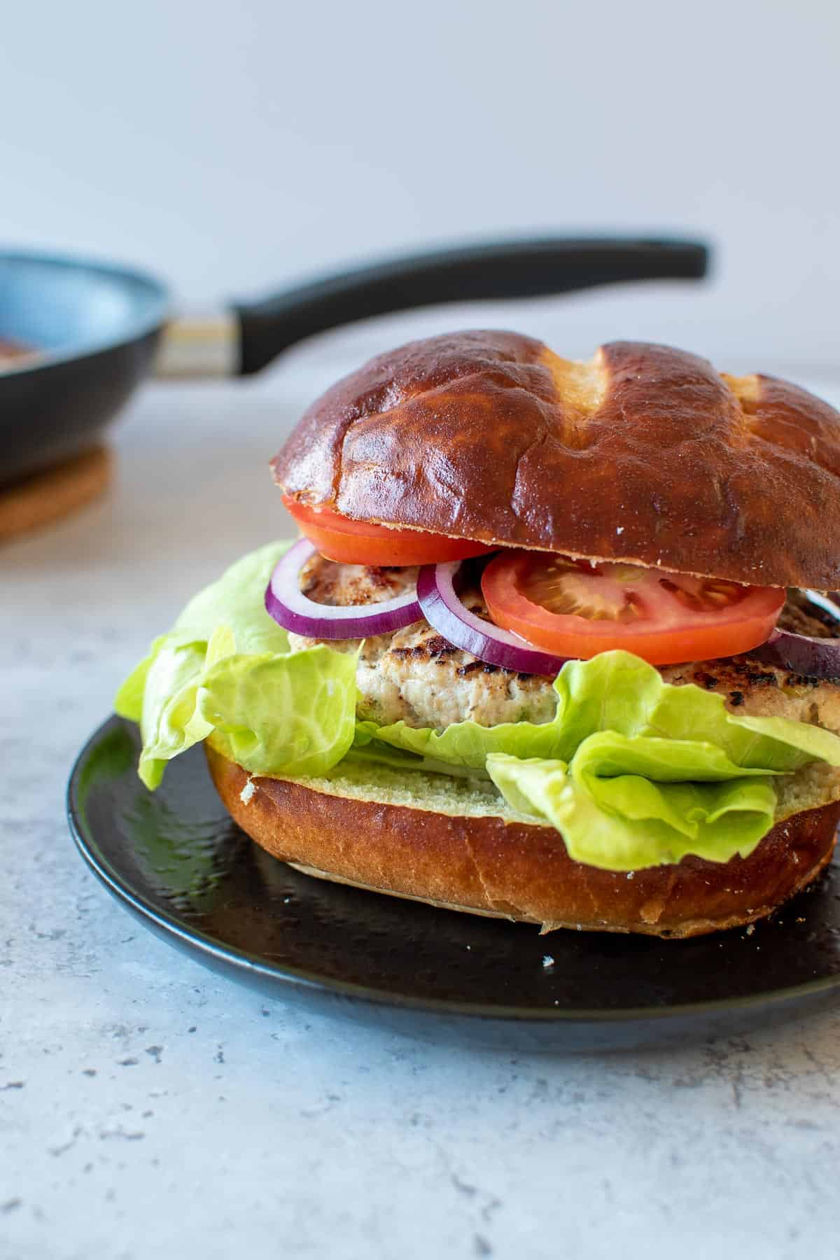 A burger on a plate, with a frying pan in the background.