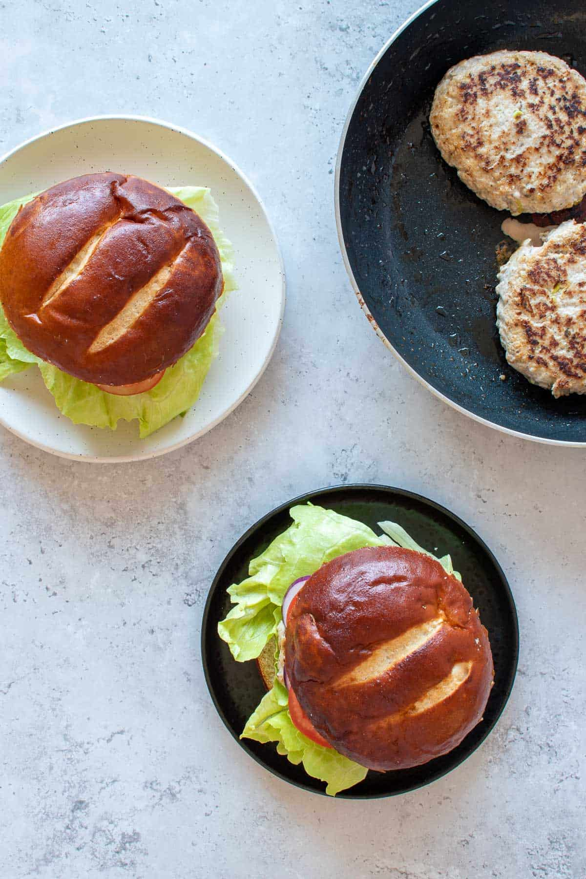 Two plated pork and apple burgers, with more burger patties in a frying pan on the side.