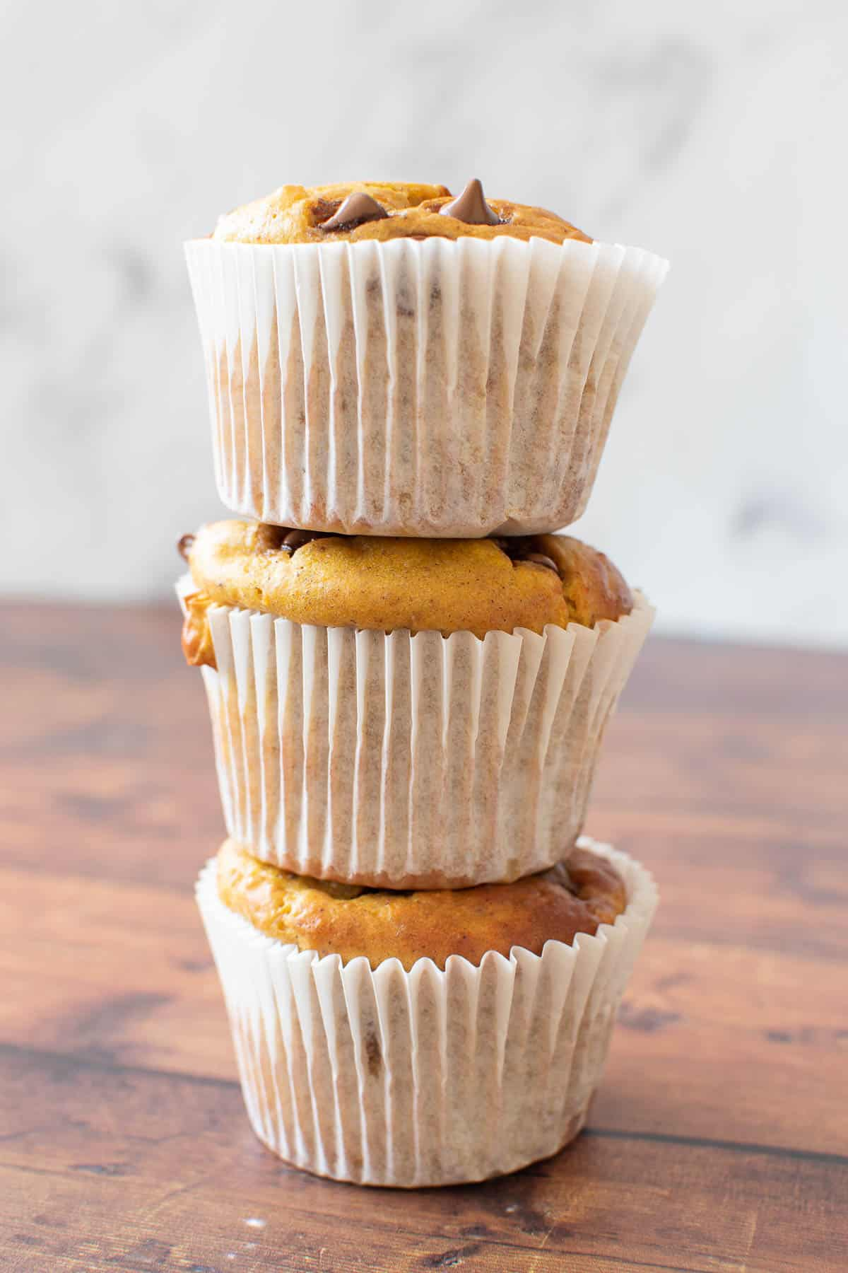 Three pumpkin chocolate chip muffins stacked on top of each other.