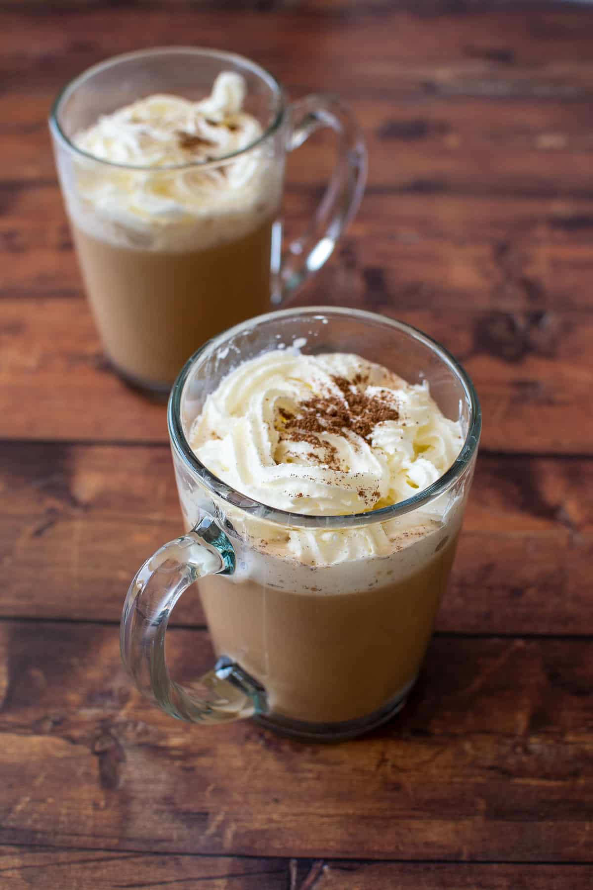 Two cups of latte with whipped cream.