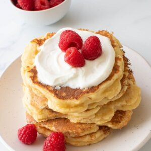 Quark pancakes topped with quark and raspberries.