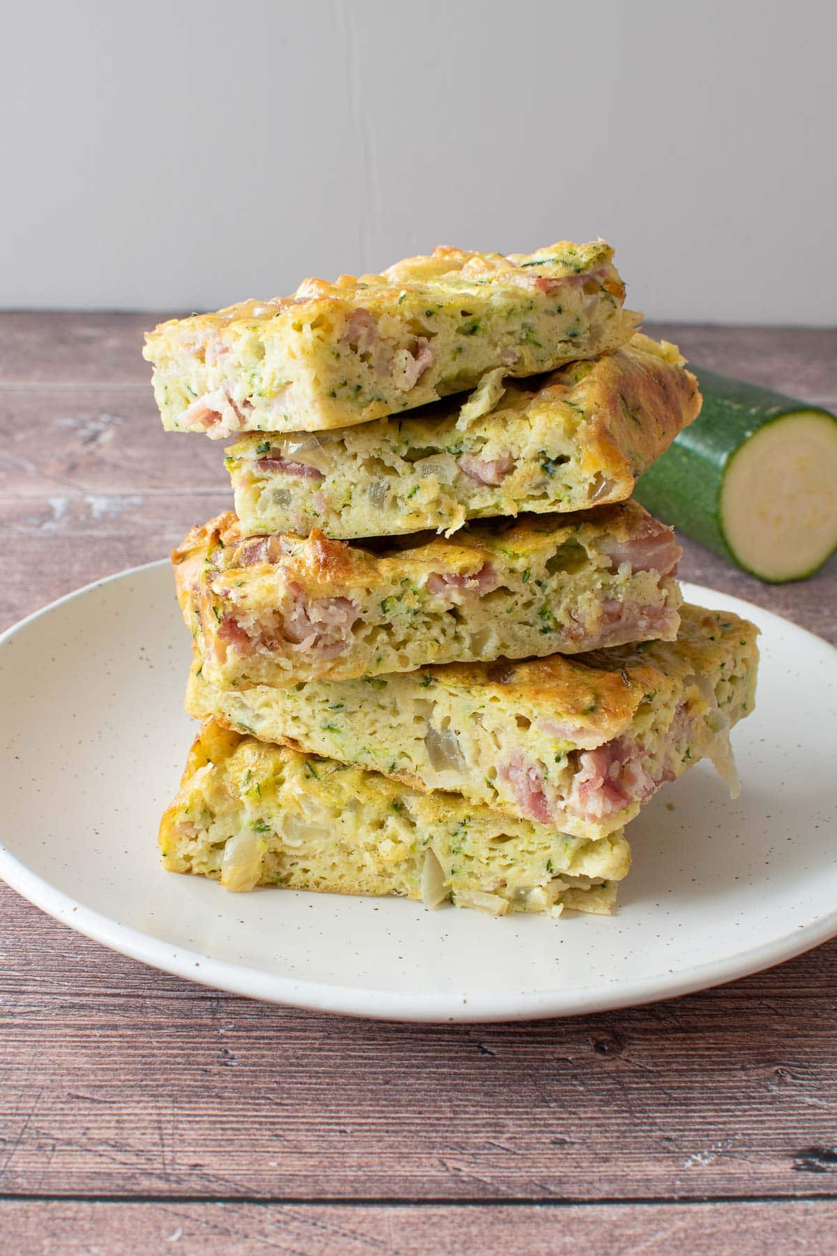 A plate of stacked zucchini slices, with zucchini in the background.