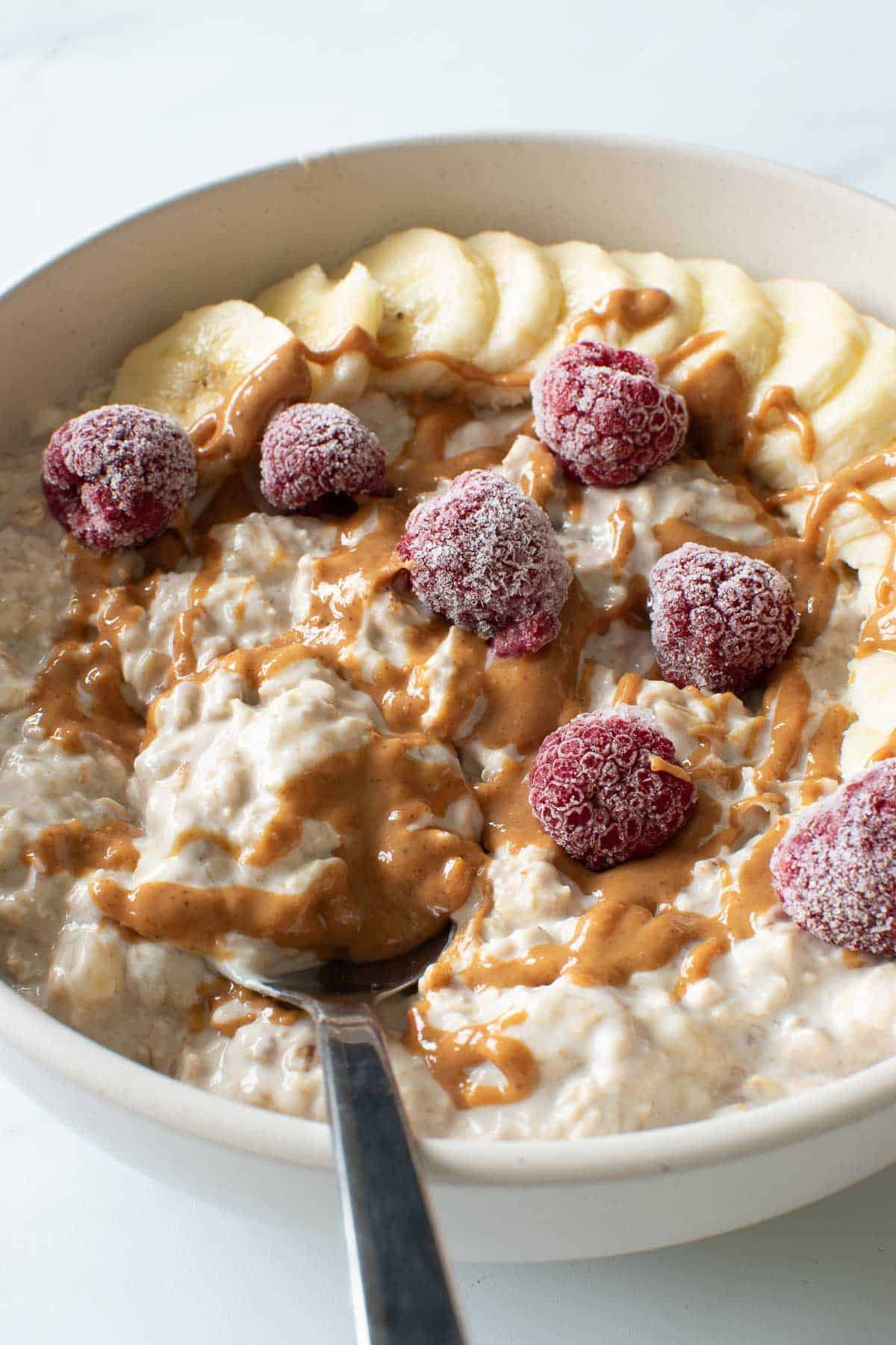 Refrigerator oatmeal with bananas. A spoon lifting out a portion.