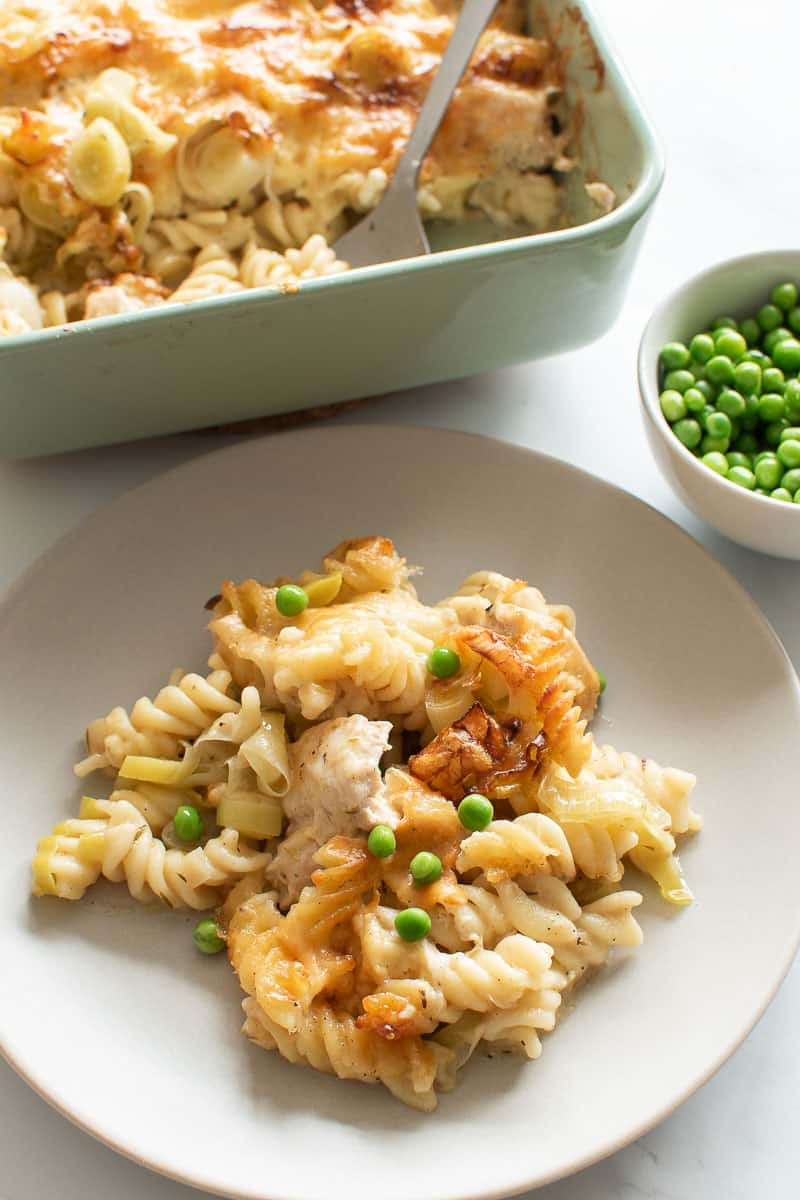 A plate of pasta bake with chicken, leek and peas, with peas and pasta bake in the background.