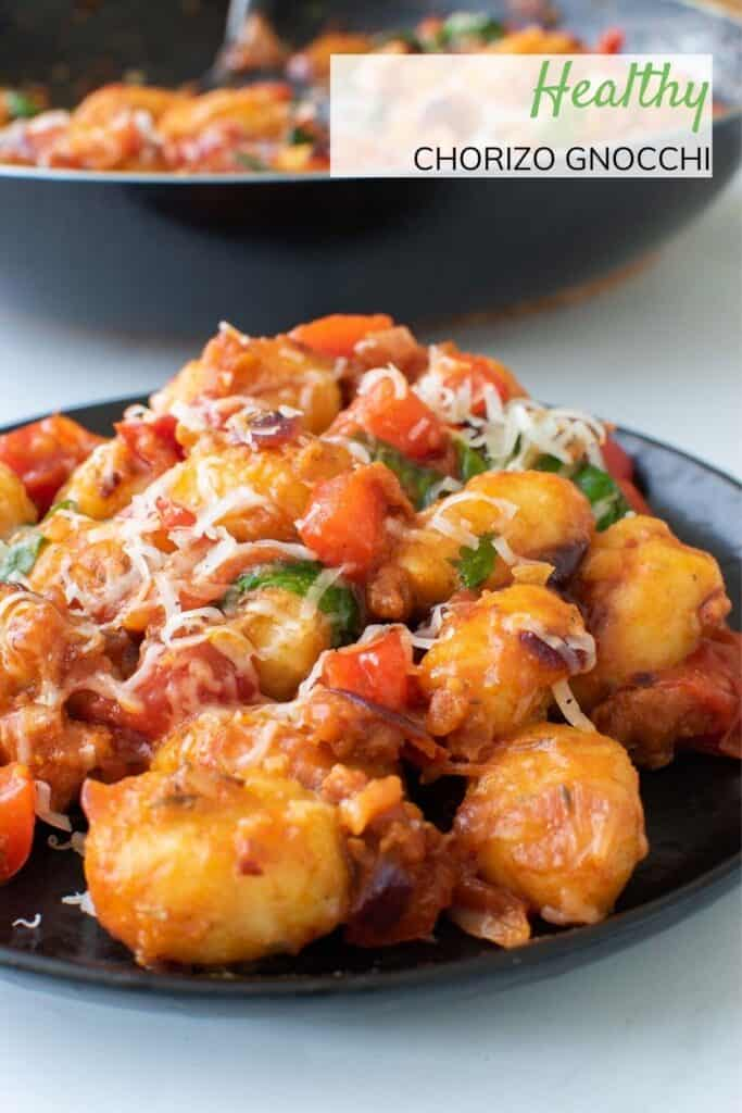 A plate of gnocchi with chorizo and tomatoes.