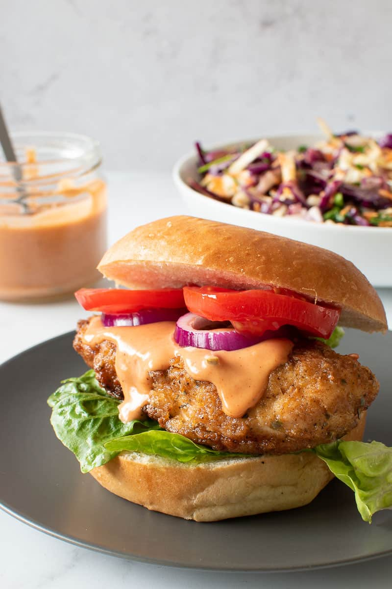 Chicken burger, with coleslaw and burger sauce in the background.