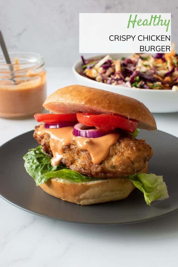 A chicken burger with lettuce, tomatoes, burger sauce and onion.