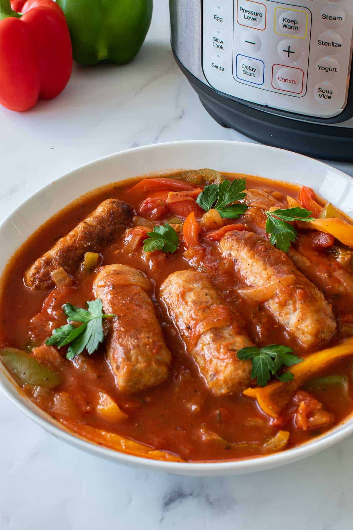 A large bowl of peppers, sausage and tomato sauce.