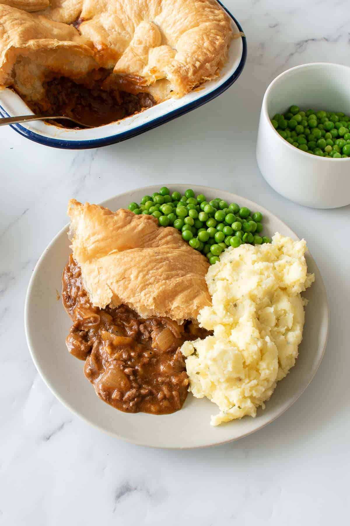 Peas, mash and pie on a plate.