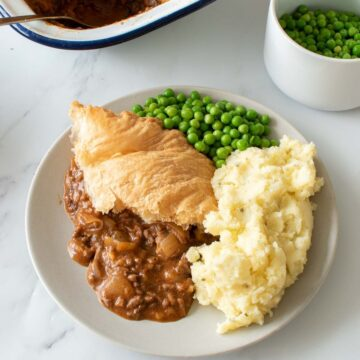 Minced beef puff pastry pie with peas and mashed potatoes.