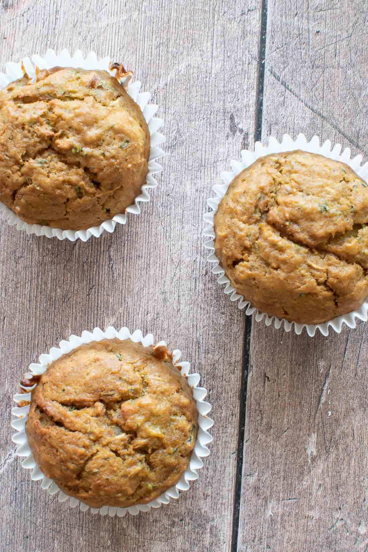 Three pumpkin zucchini muffins on a table.