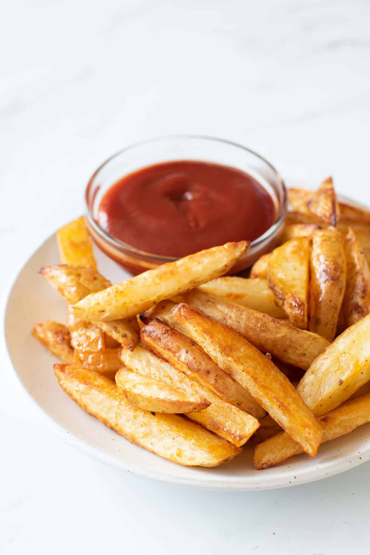 Baked french fries and ketchup.