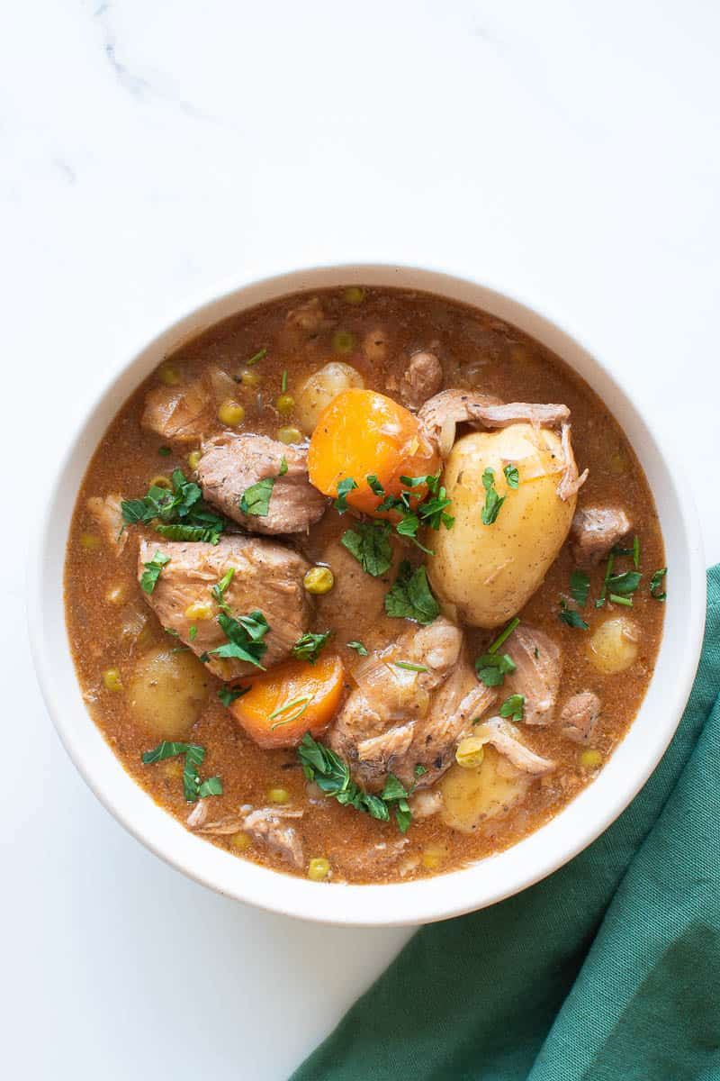 A bowl of slow cooker pork casserole with potatoes.