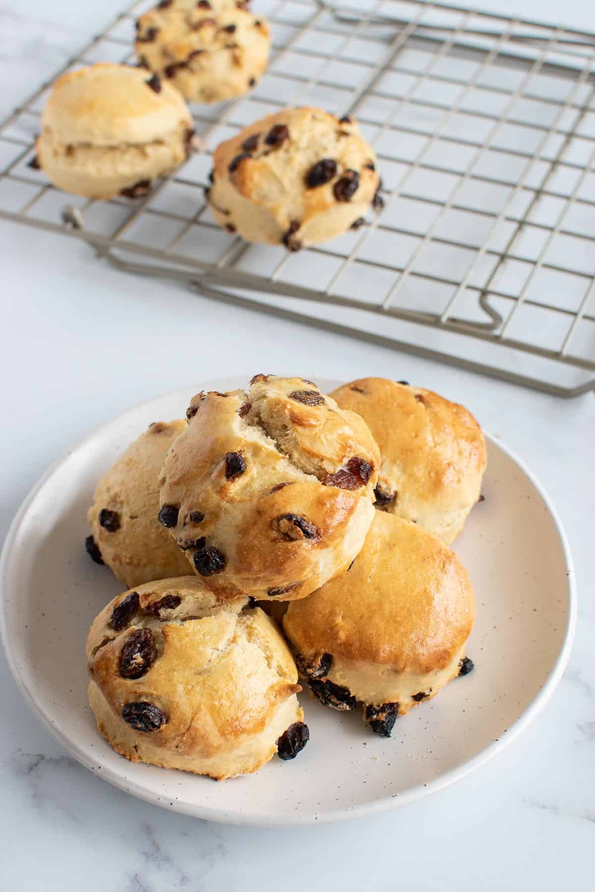 A plate of scones, with more scones resting on a cooling rack in the background.