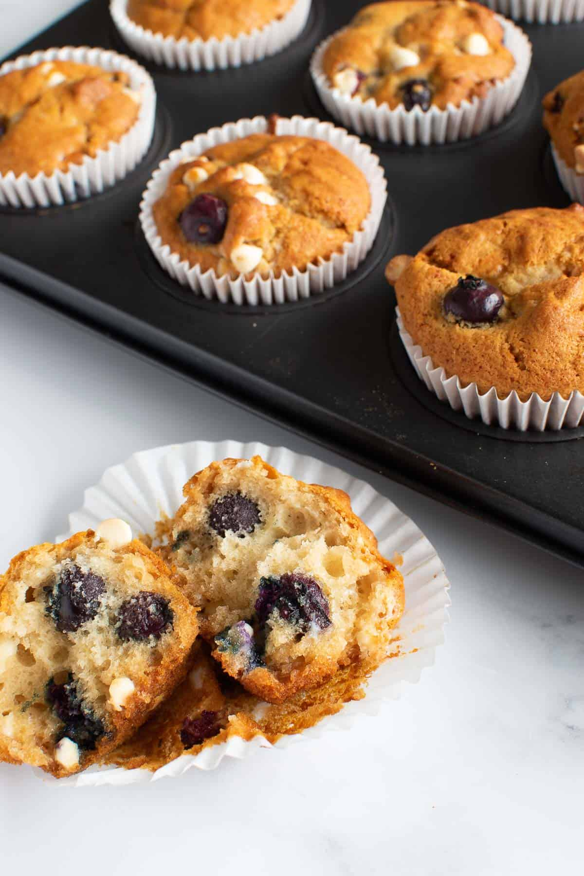 A halved blueberry and white chocolate muffin, with more muffins in the back.