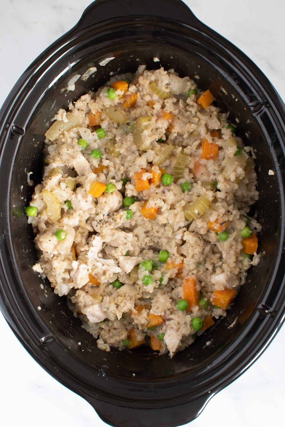 Chicken, rice and vegetables in a crockpot.