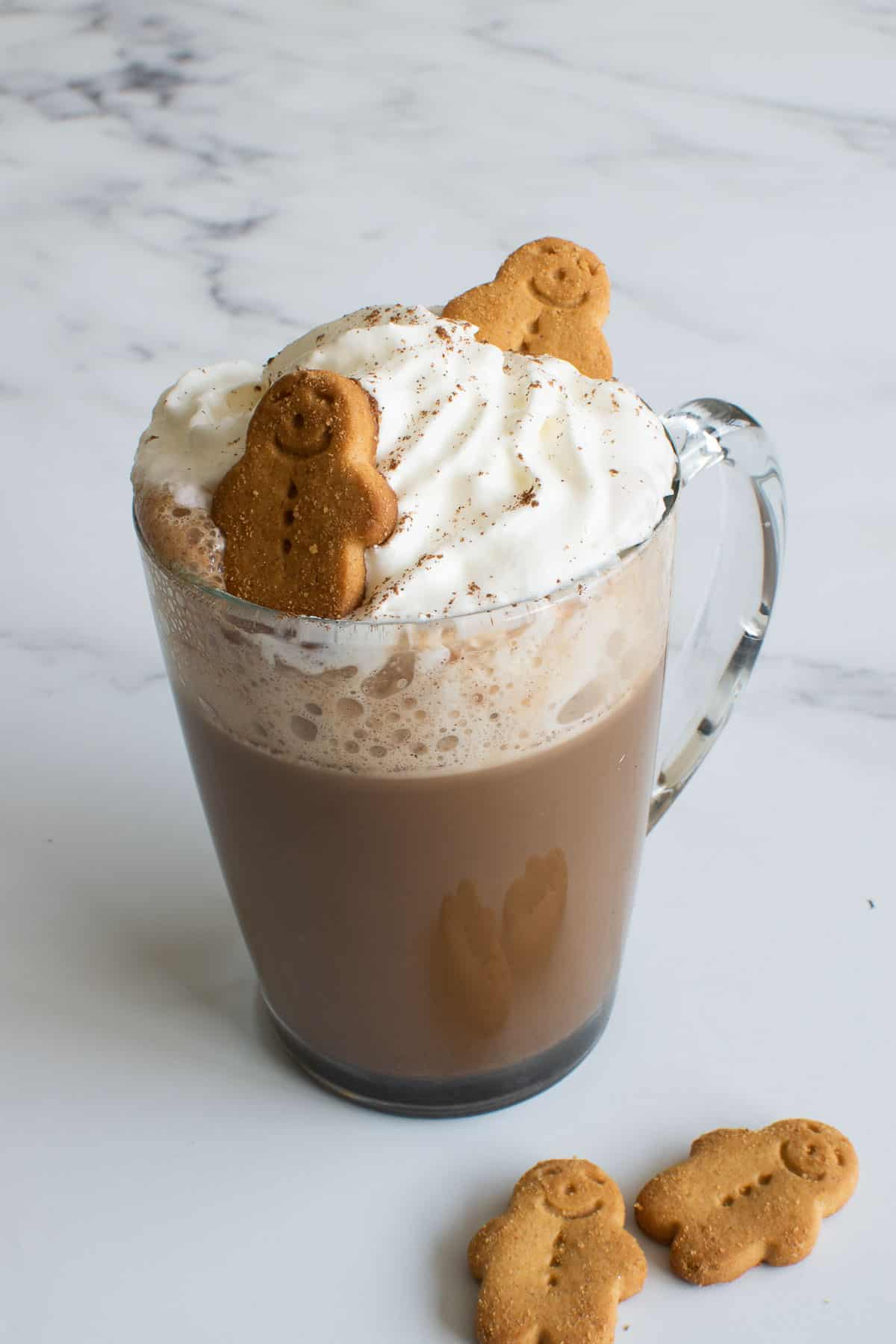 A glass of gingerbread latte with whipped cream and gingerbread men.
