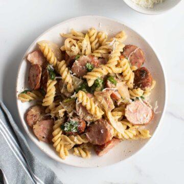 Pasta with kielbasa sausage on a plate.